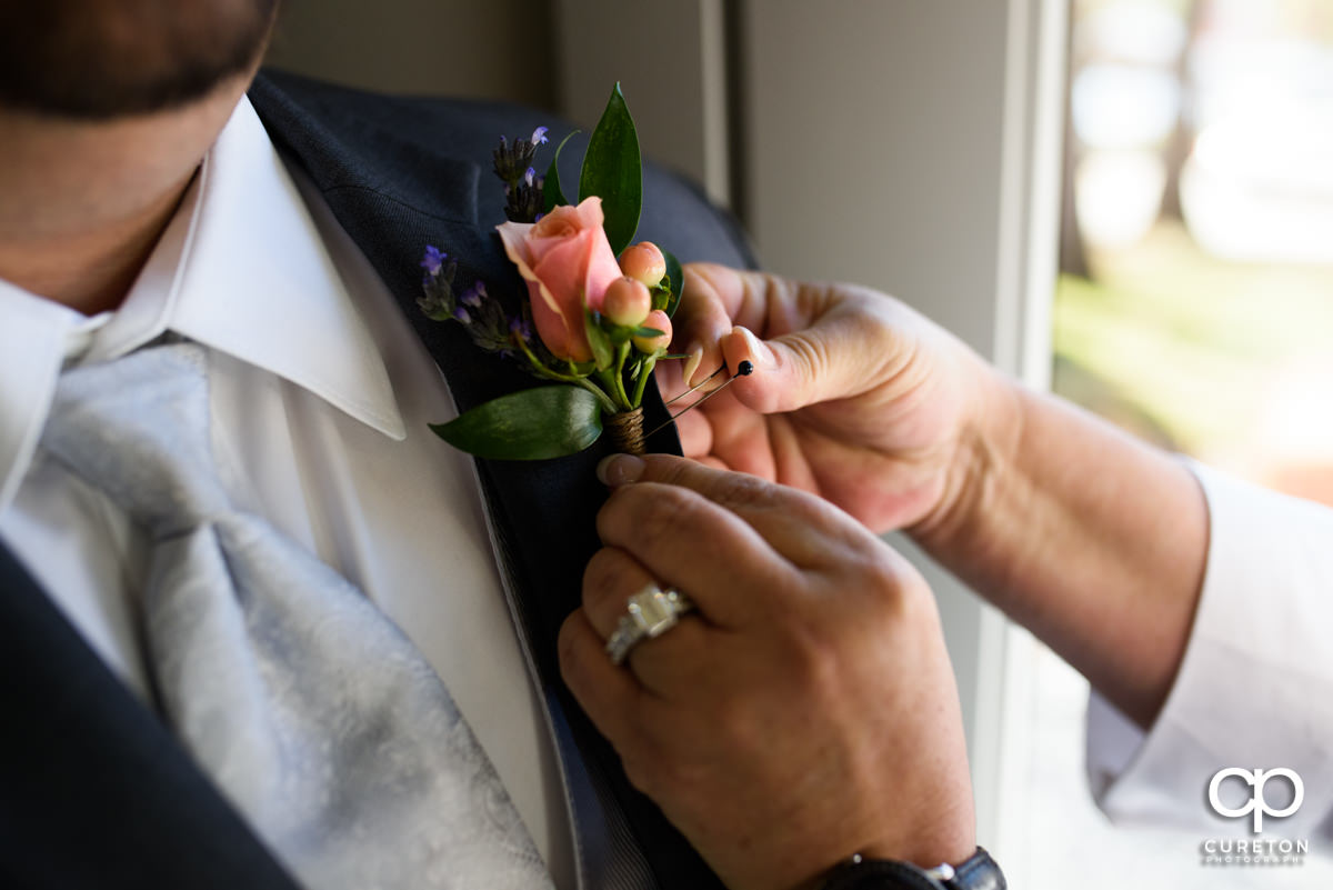Groom getting his boutonniere pinned on.