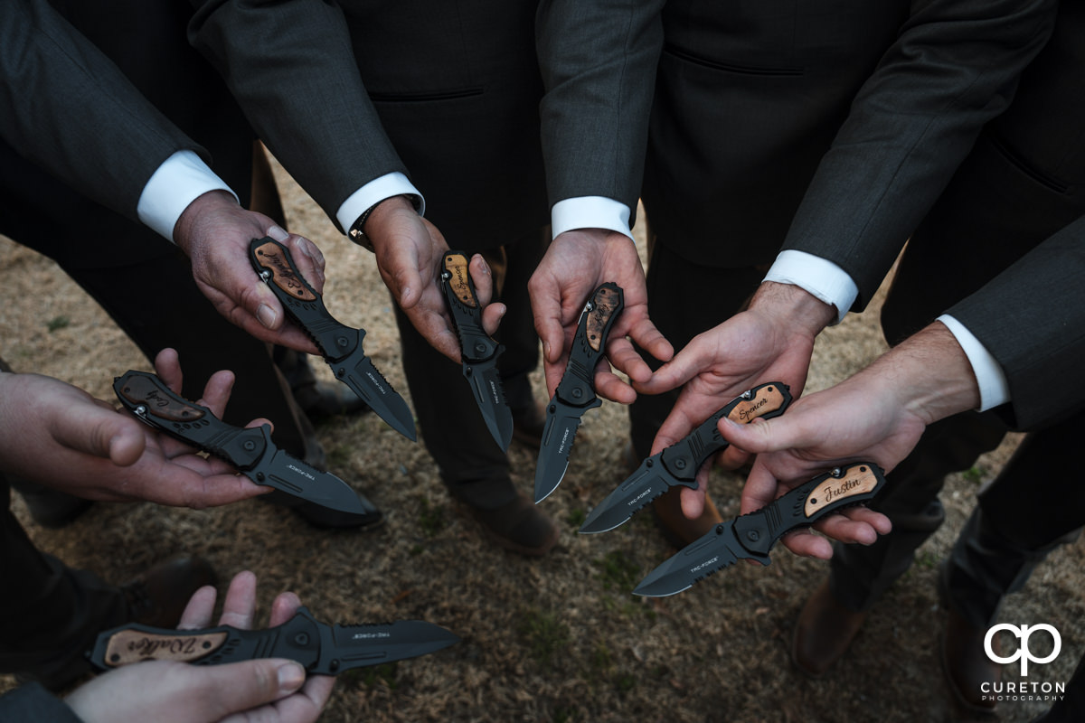 Groomsmen showing off their knives.