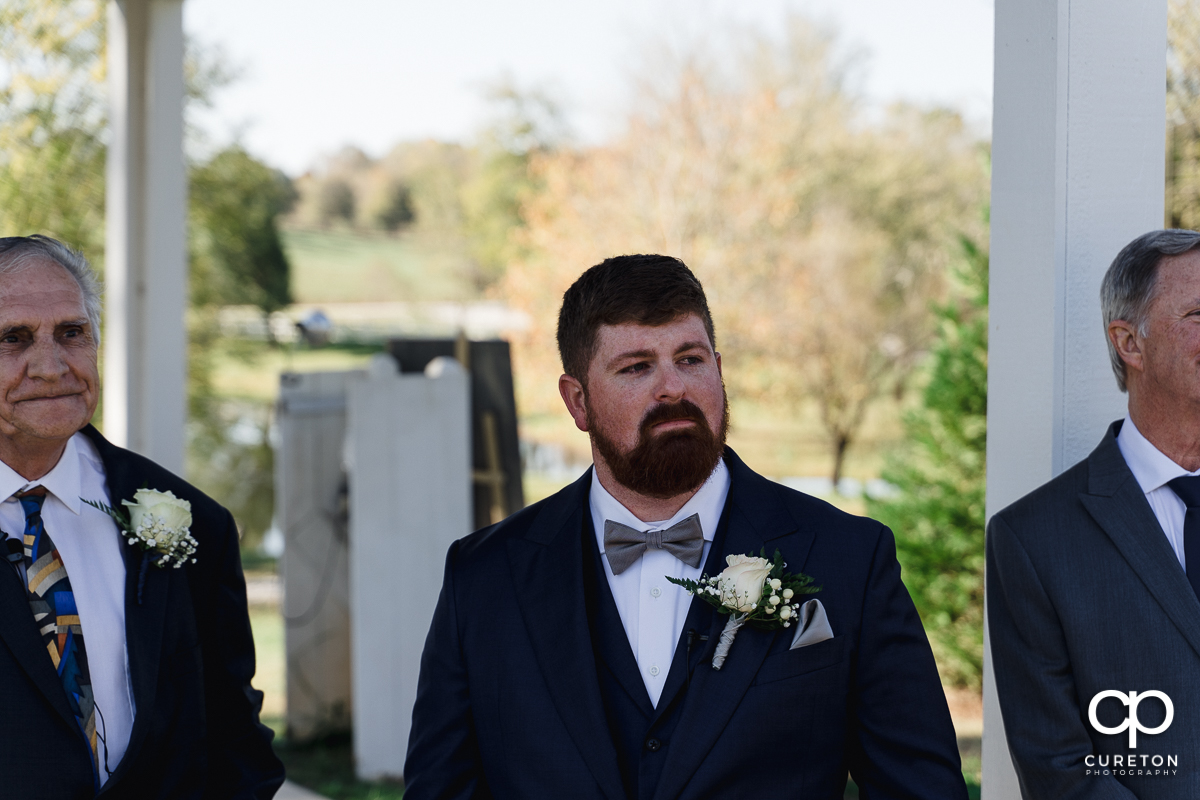 Groom seeing his bride walking down the aisle at their South Wind Ranch wedding.