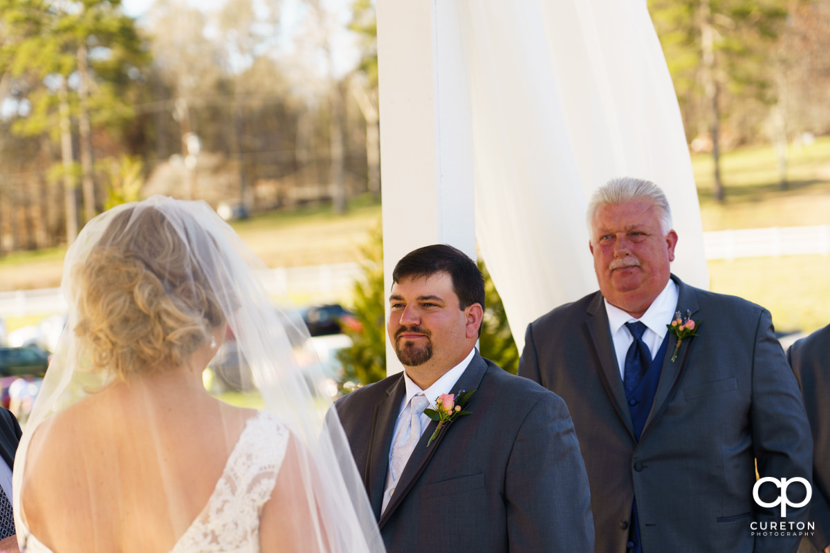 Groom smiling at his bride during the ceremony.