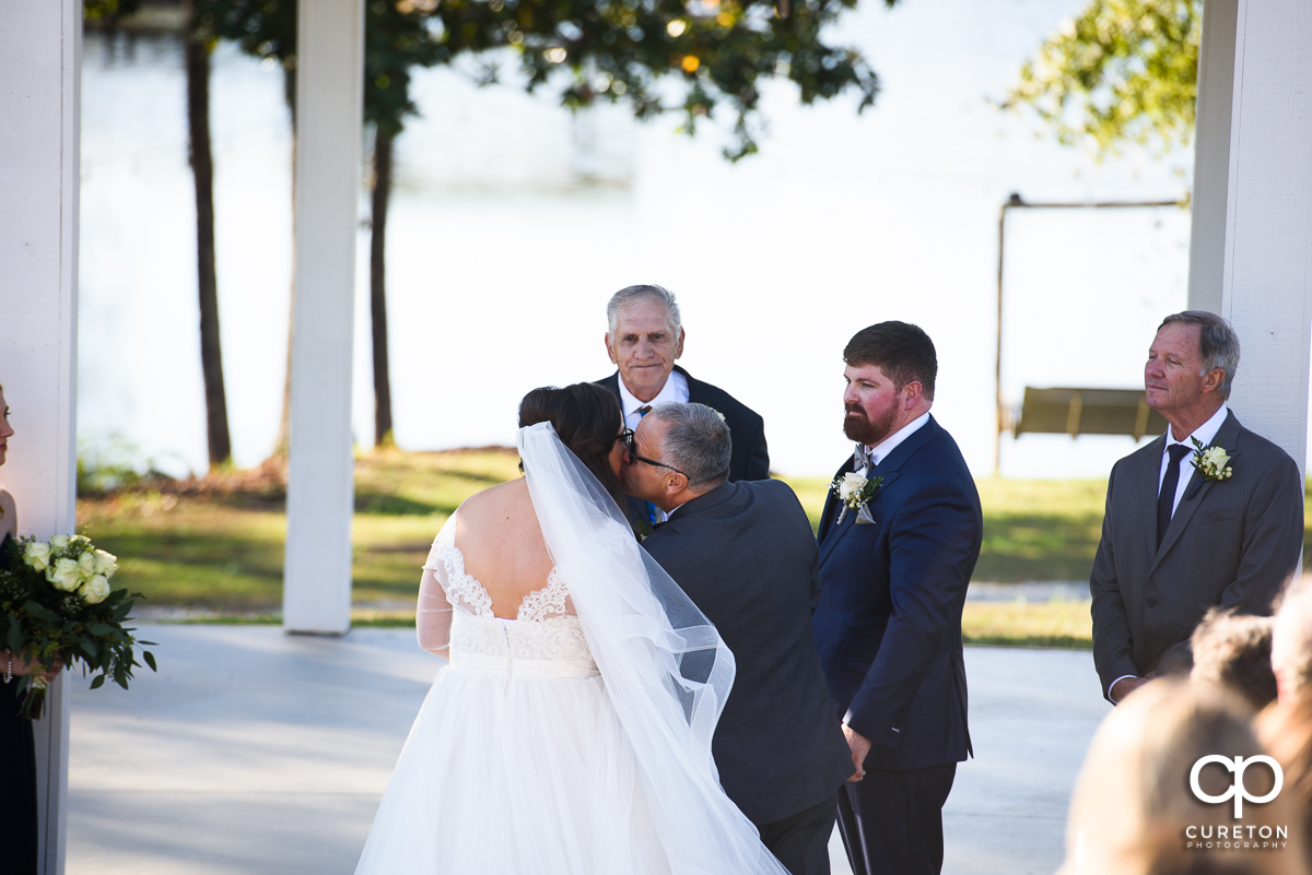 Bride's dad kissing her on the cheek at the wedding ceremony.