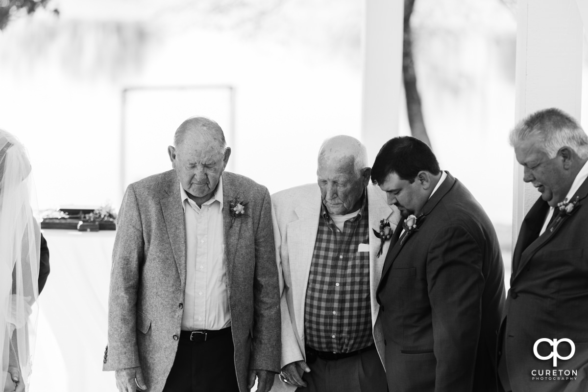 Groom praying with his grandfathers at the wedding ceremony.