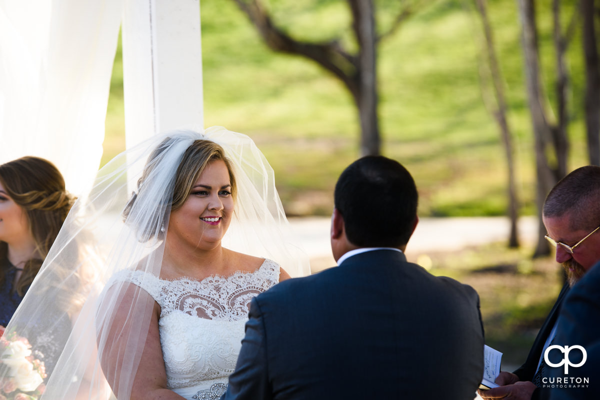 Bride smiling at her groom during the wedding ceremony.