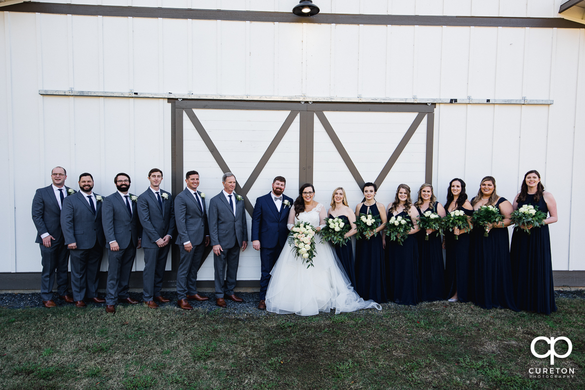 Wedding party in front of the white barn doors at South Wind Ranch.