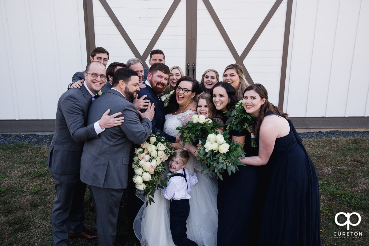The entire wedding party hugging the brode.