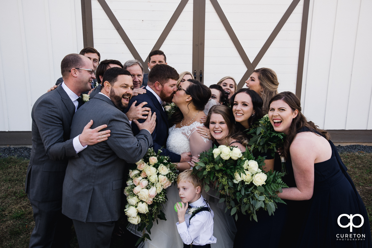 The bride and groom kissing as their wedding party all hugs them at once.