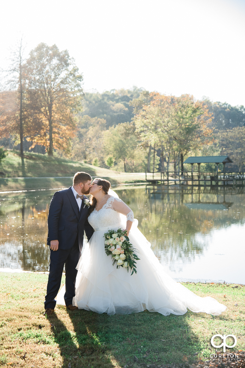 Bride and groom kissing in front of the lake at South Wind Ranch.