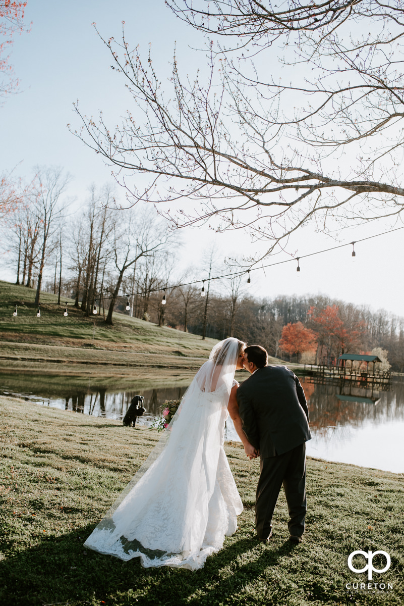 Bride and groom kissing and holding hands by the lake during their South Wind Ranch wedding in Travelers Rest,SC.