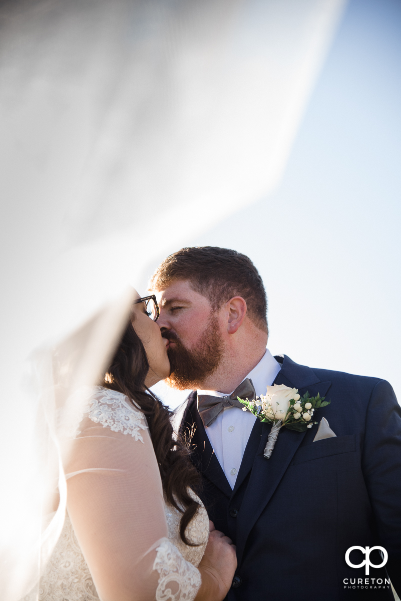 Bride and groom kissing underneath the veil.