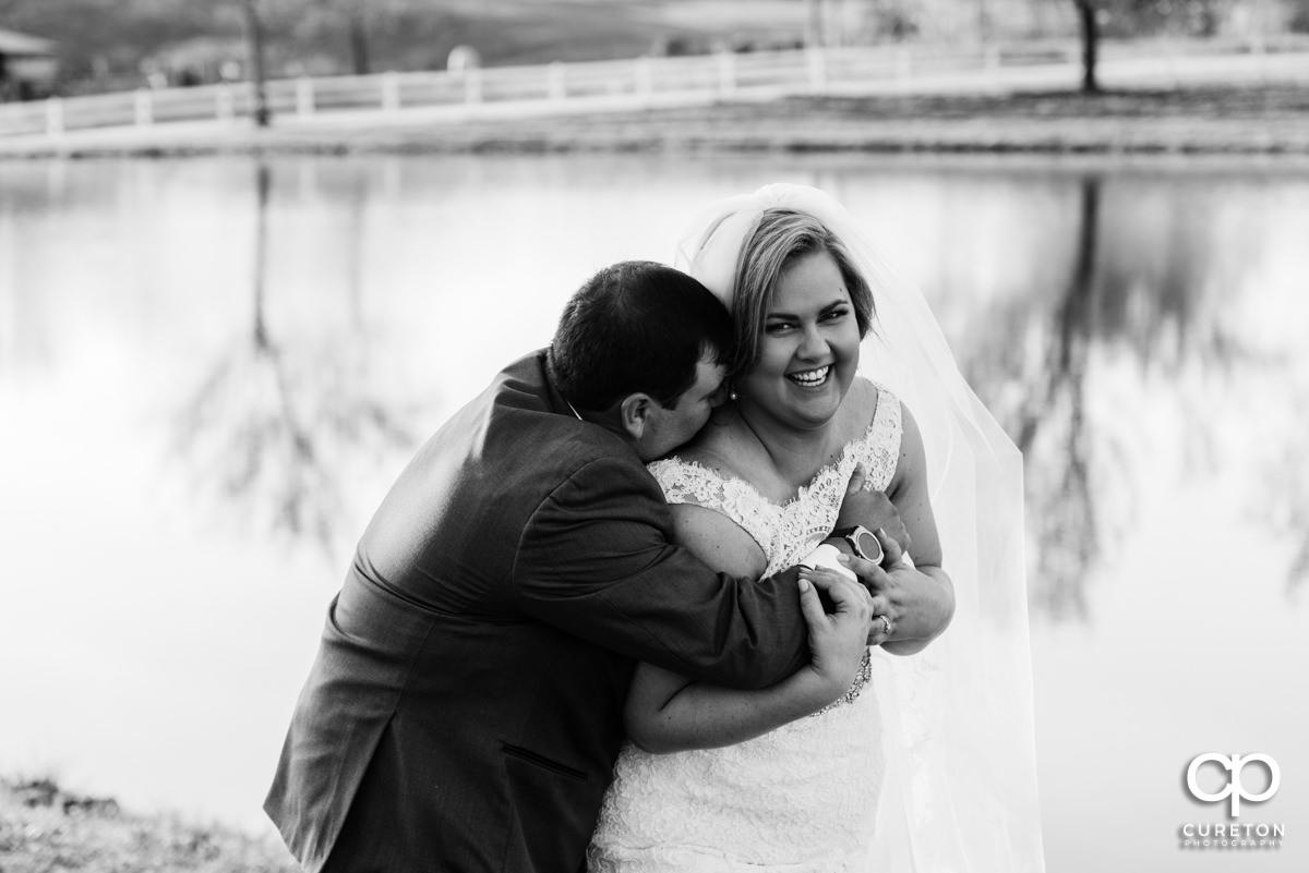 Groom hugging the bride.