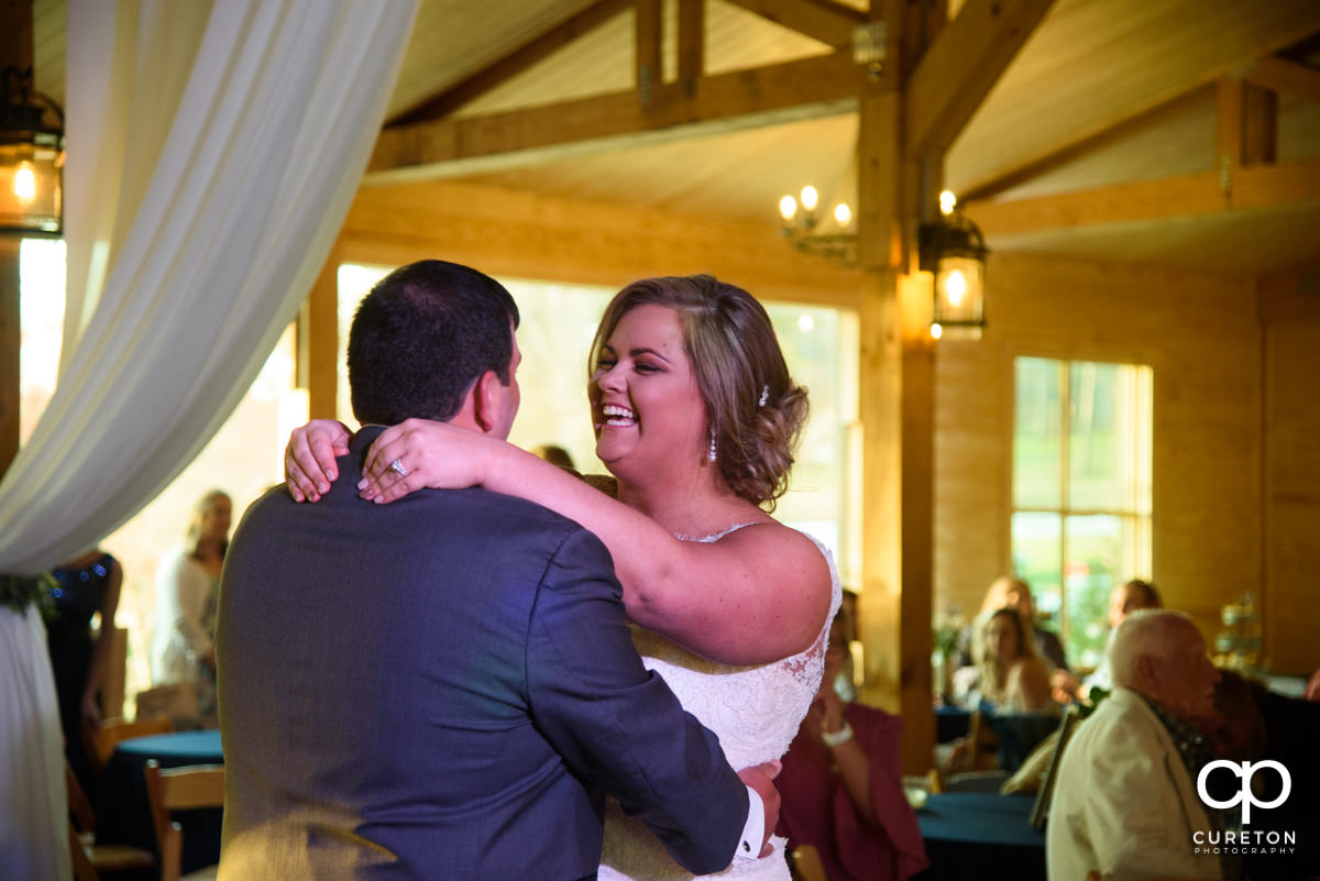 Bride laughing during the first dance during their South Wind Ranch wedding in Travelers Rest,SC.