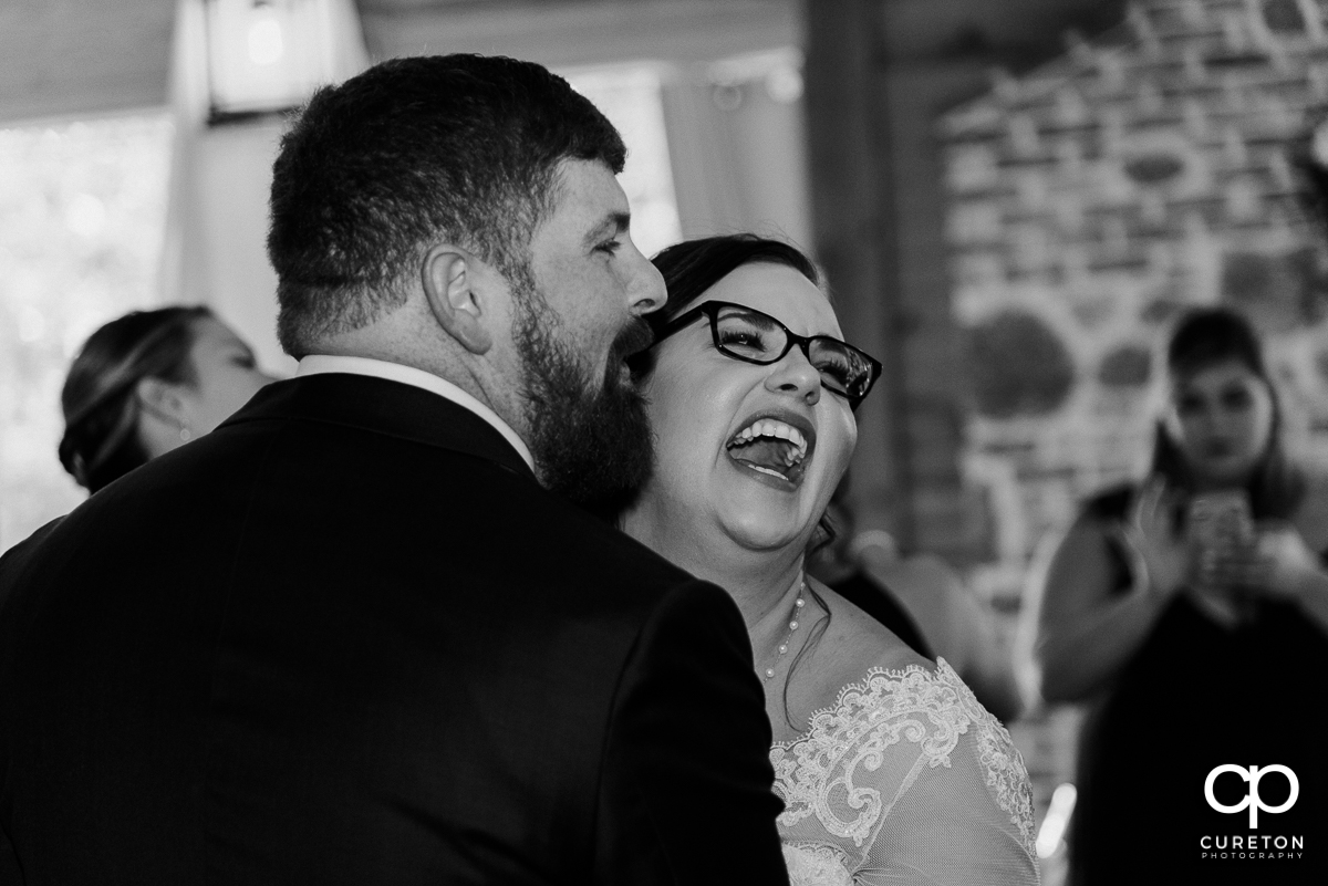 Bride and groom laughing during their first dance.