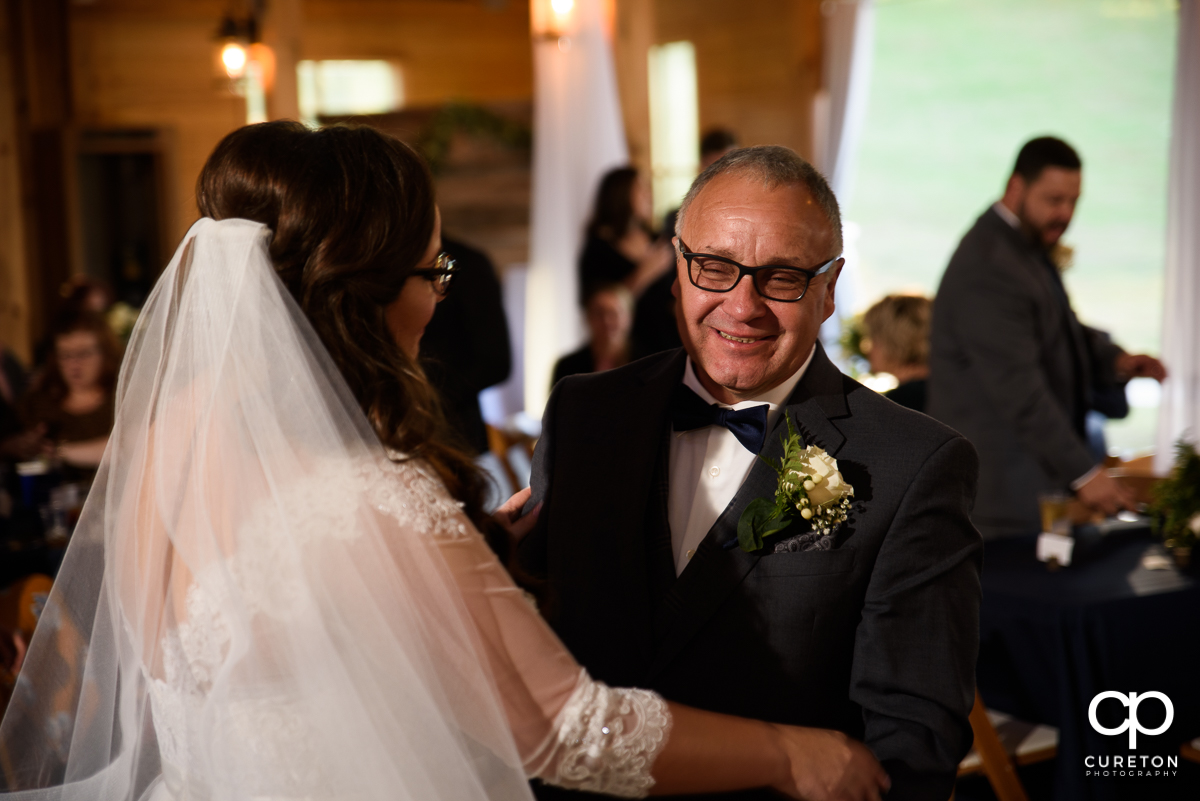 Bride's father smiling after sharing a dance with his daughter at her wedding.