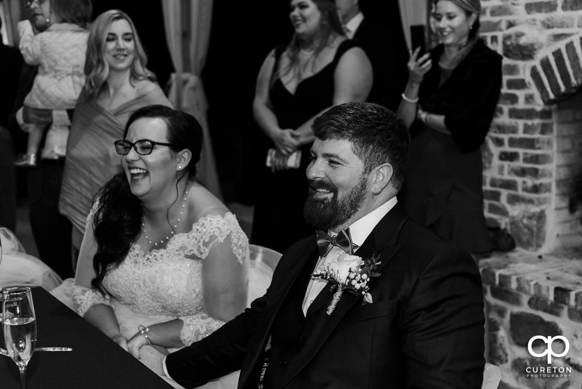 Bride and groom laughing at a speech.