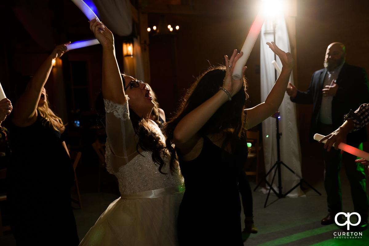 Wedding guests dancing at the reception while holding glow sticks.