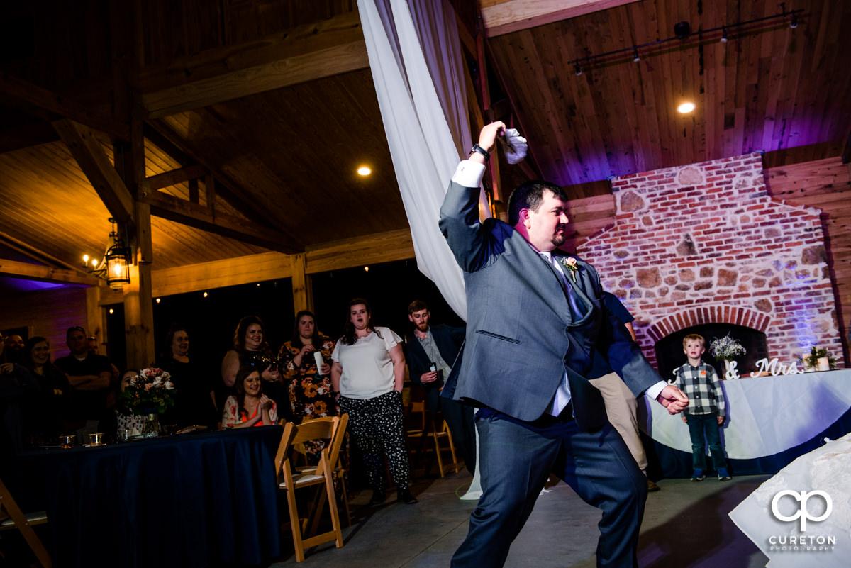 Groom dancing with the garter.