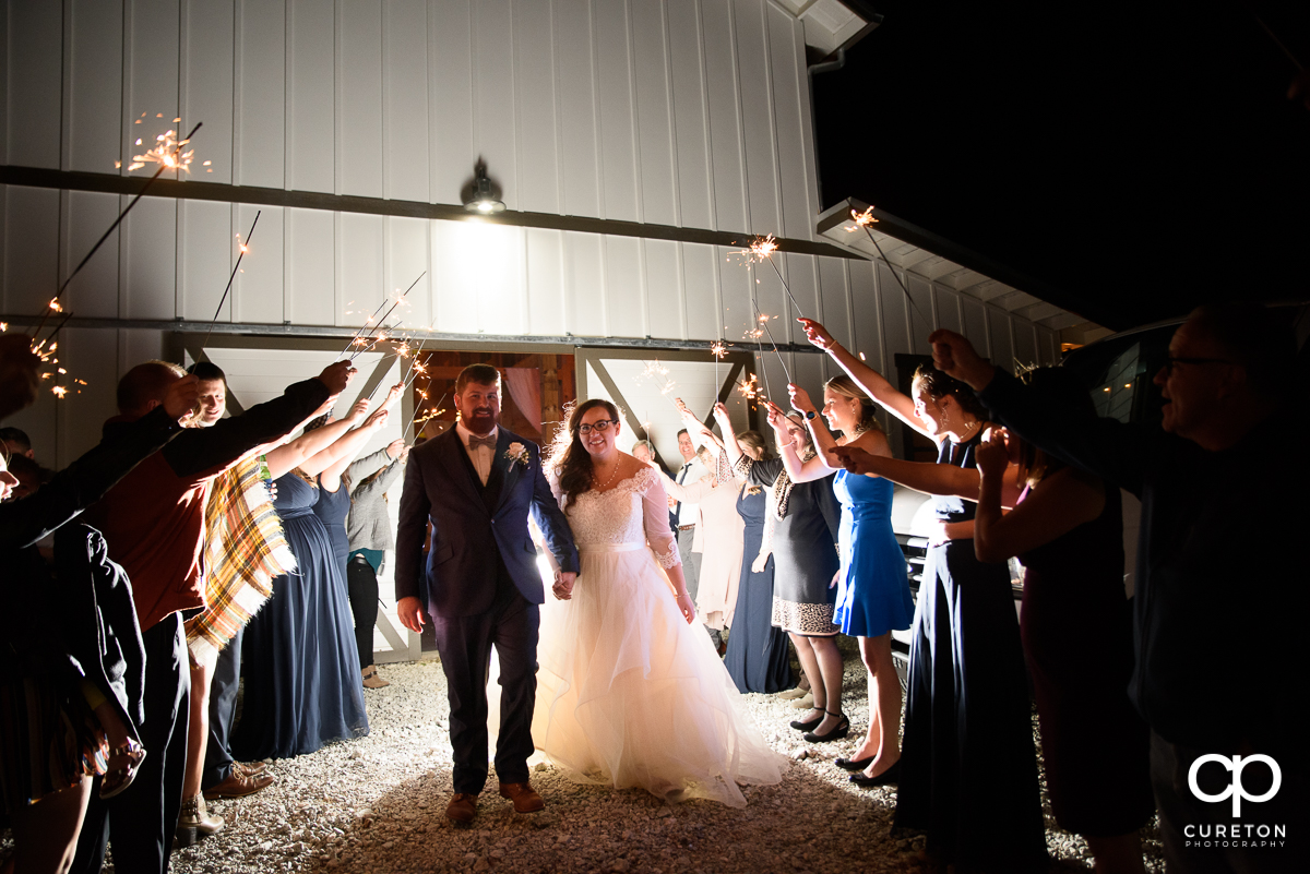 Bride and groom making a grand exit as their guests hold up sparklers.
