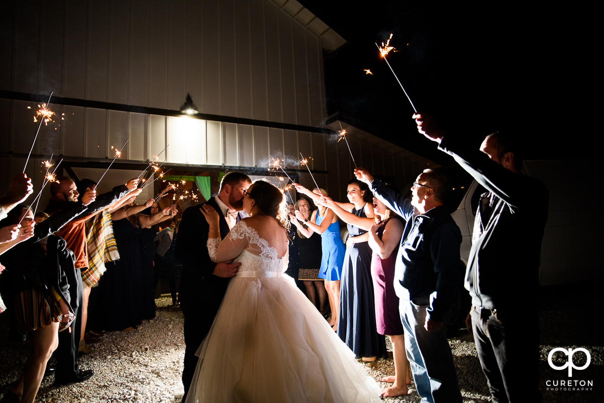 Bride and groom making a grand exit as their guests hold up sparklers at South Wind Ranch.