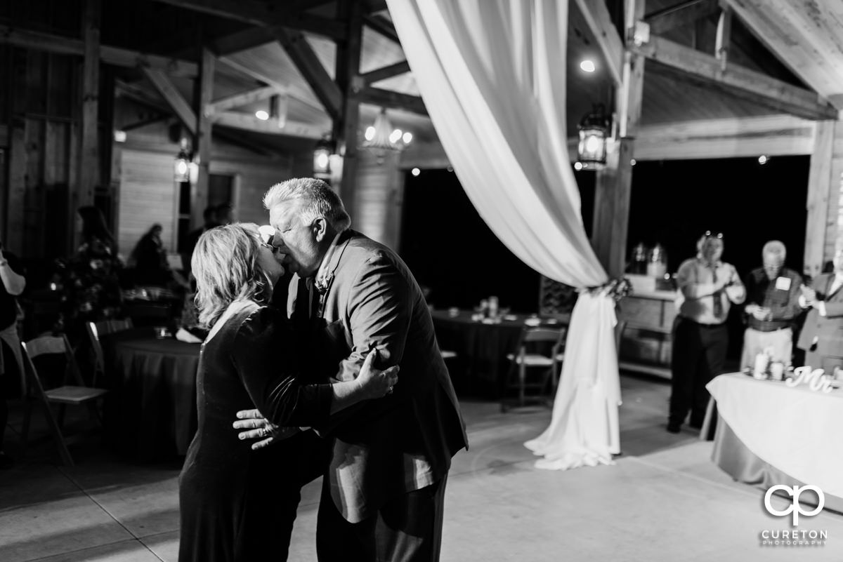 Groom's parents sharing a dance and a kiss.