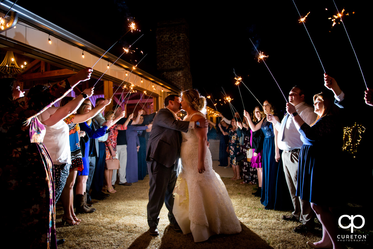 Bride and groom kissing during a grand exit through sparklers at their South Wind Ranch wedding in Travelers Rest,SC.
