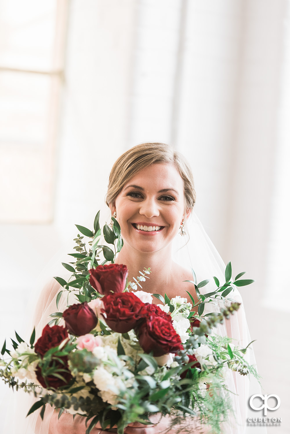Bride smiling holding a beautiful bouquet by Culpepper Designs.