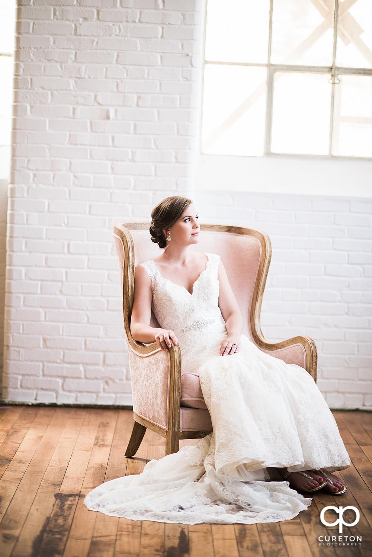 Bride sitting in a chair in window light.