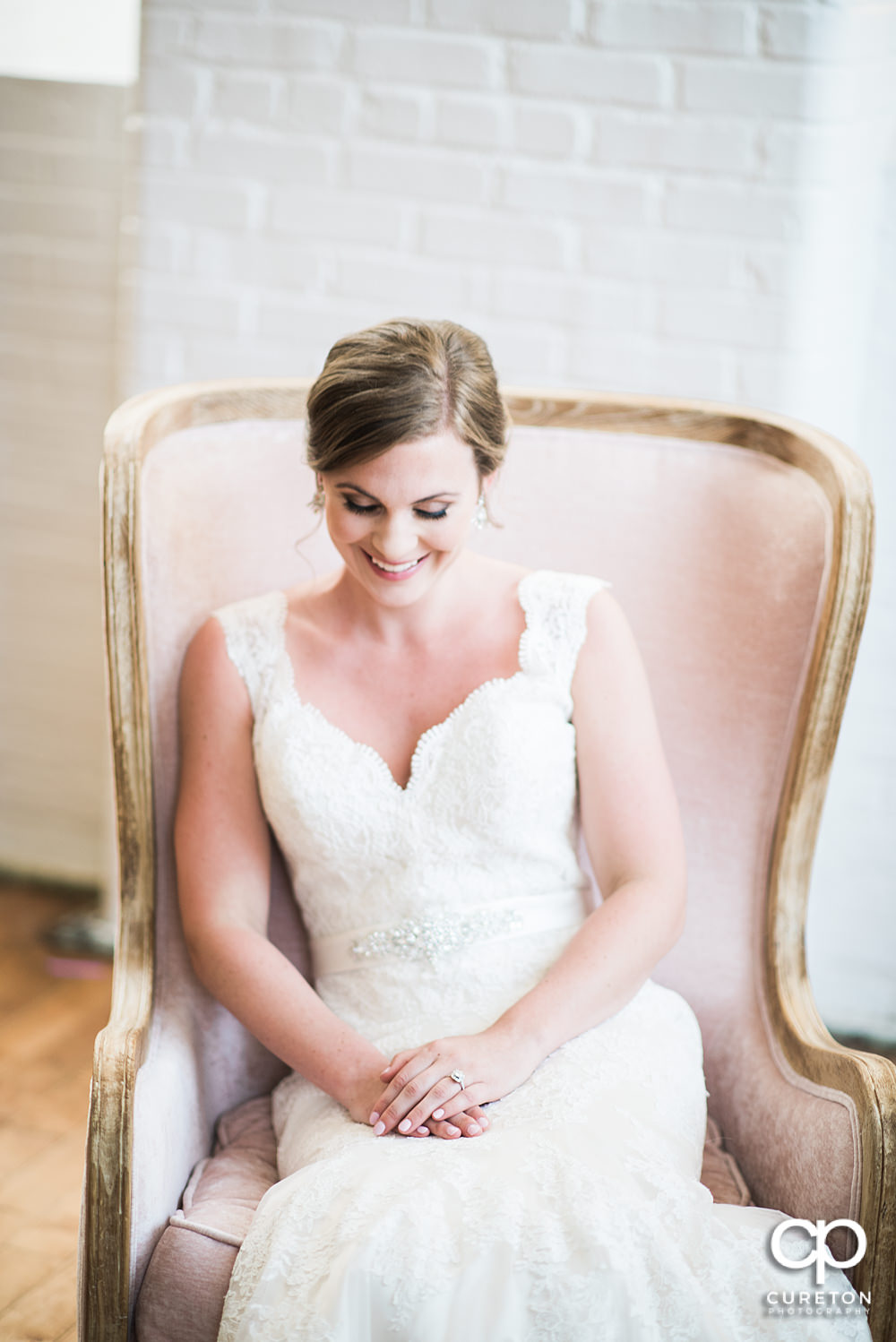 Bride sitting in a chair in the middle of the Southern Bleachery wedding venue.