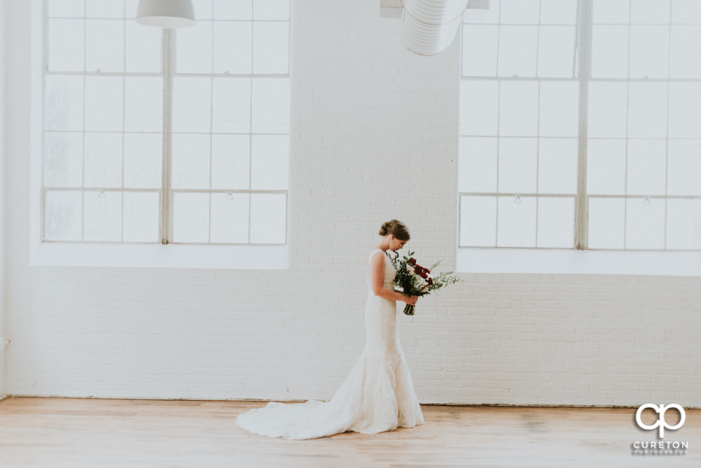 Bride smelling her bouquet during her bridal session at The Southern Bleachery wedding venue at the Taylor Mill.
