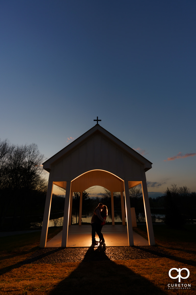 Man kissing his bride in the chapel at sunset during a pre wedding South Wind Ranch engagement session in Travelers Rest,SC.