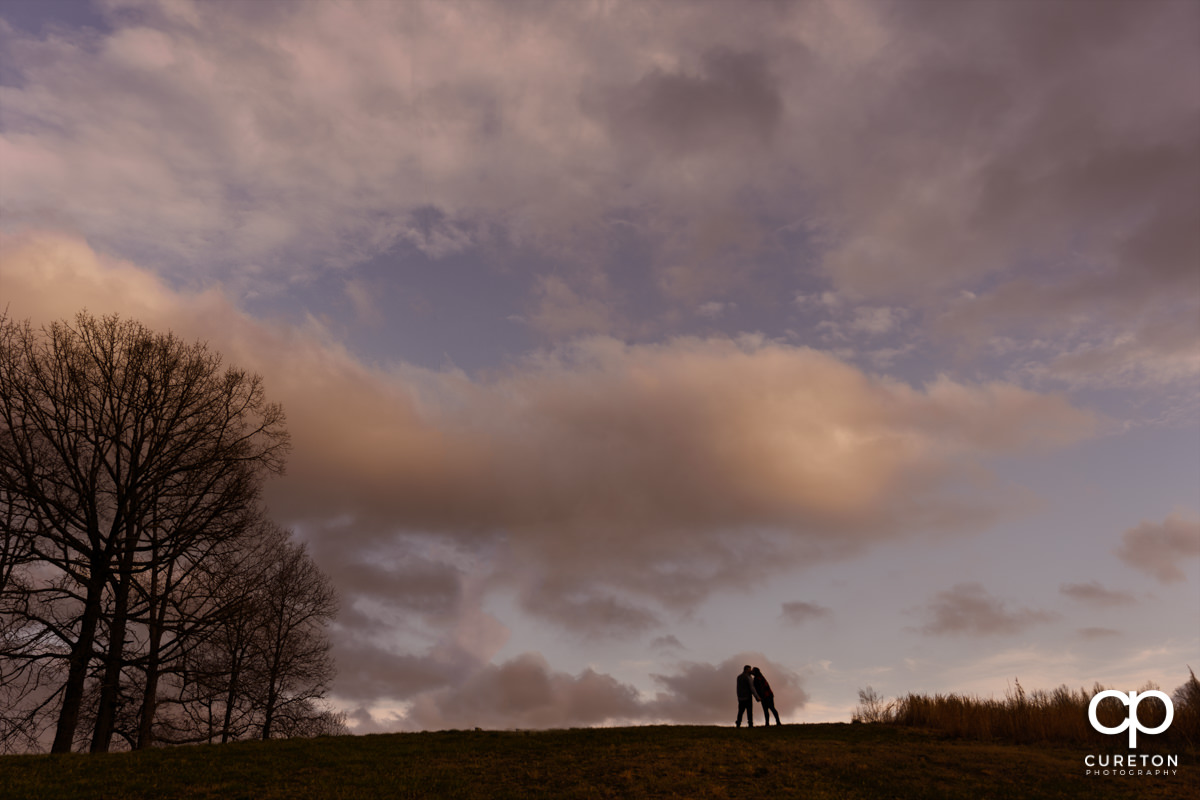 Couple kissing at sunset in the field during a pre wedding South Wind Ranch engagement session in Travelers Rest,SC.
