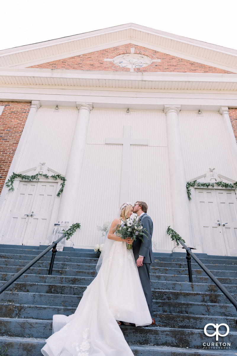 Groom kissing his bride on the forehead on the steps of the church before their wedding reception at South Wind Ranch.