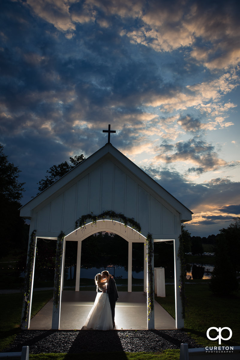 Bride and groom kissing in the outdoor chapel at sunset during their wedding reception at South Wind Ranch in Travelers Rest,SC.