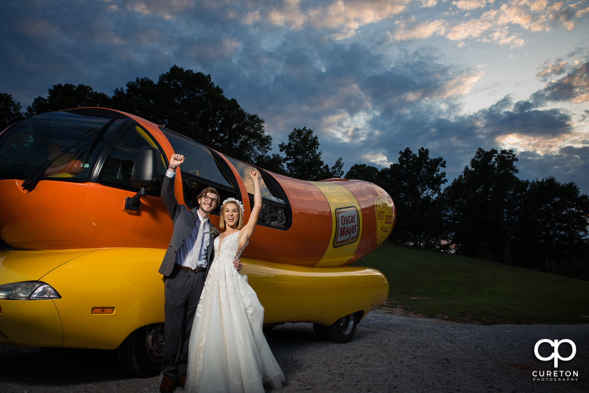 Bride and groom cheering beside the Oscar Mayer Weinermobile after their wedding.