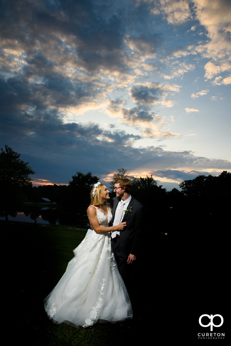 Bride and groom holding hands at sunset outside during their wedding reception at South Wind Ranch in Travelers Rest,SC.