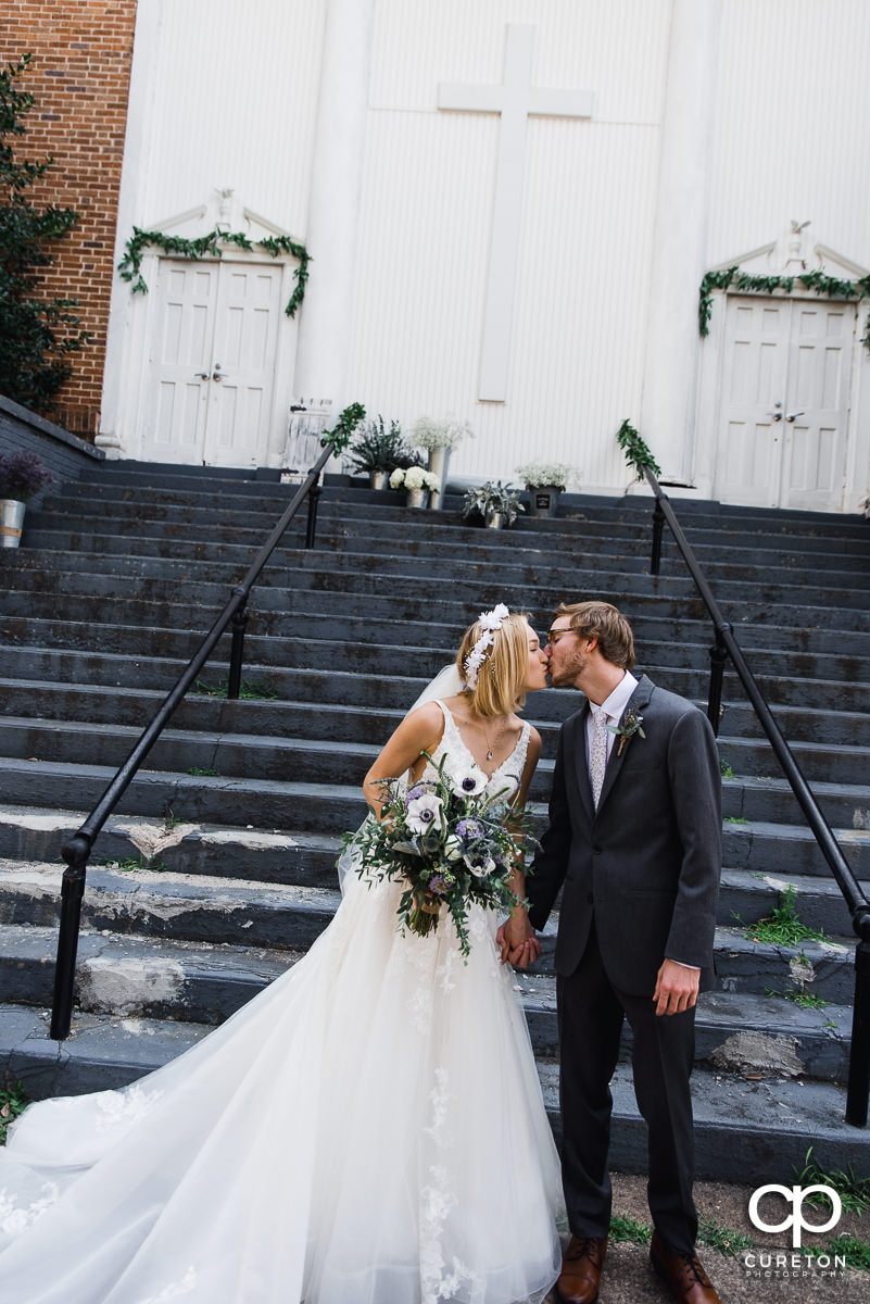 Groom kissing his bride on the steps of the church in Greenville,SC.