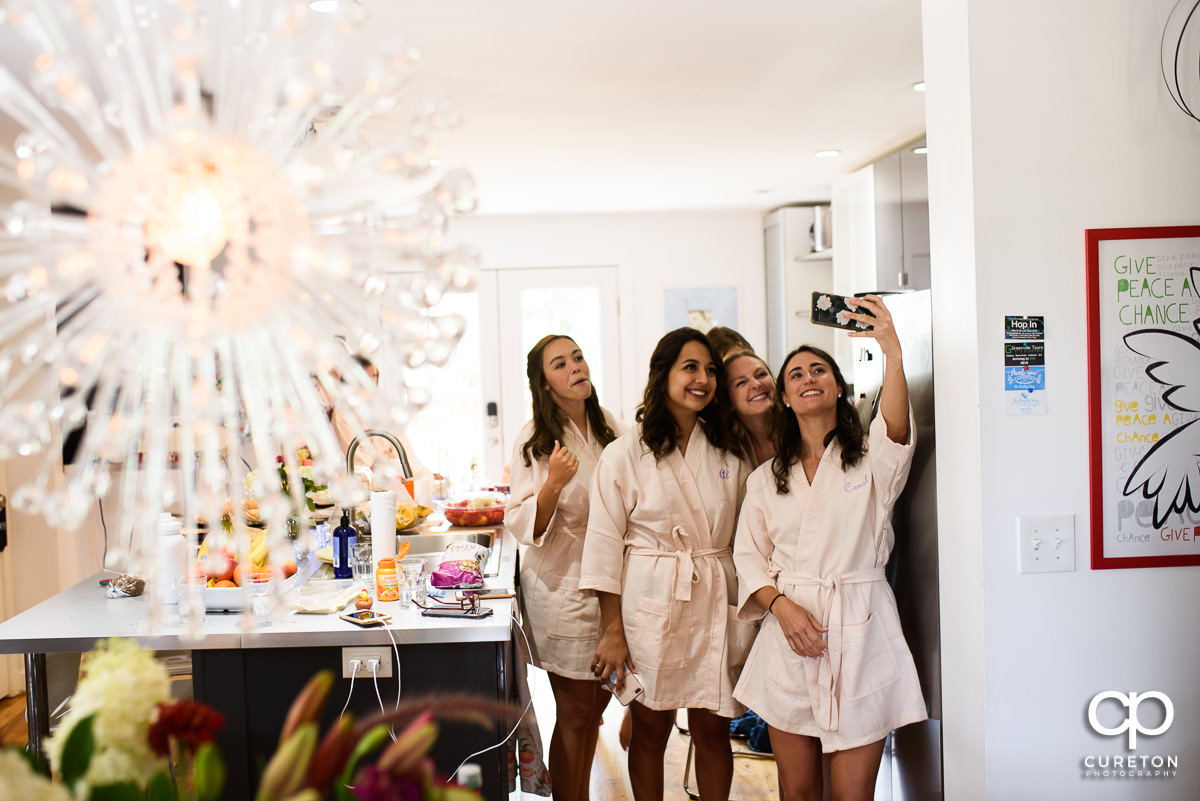 Bridesmaids taking a selfie while getting ready for the wedding at the Swamp Rabbit Inn.