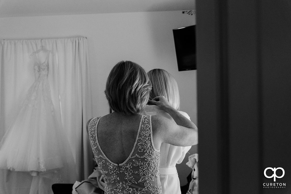 Bride's mom helping her into her dress.