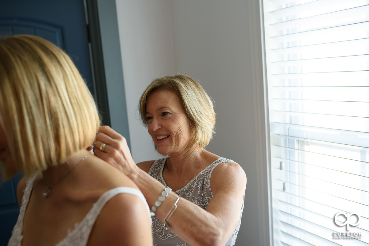 Bride's mother helping her get ready for her wedding.