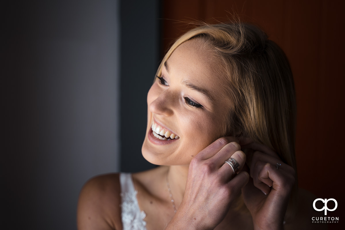 Bride smiling while putting on her earrings.