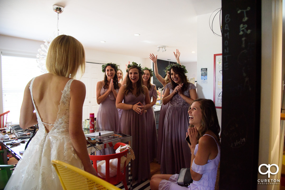 Bridesmaids smiling as they see the bride in her dress for the first time.