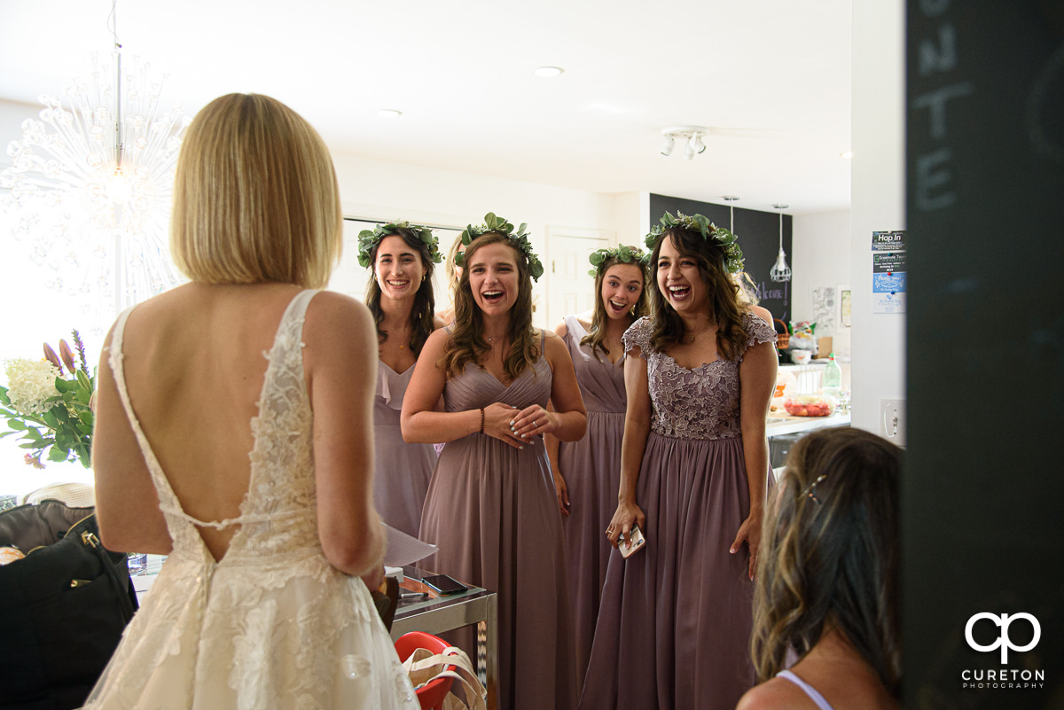 Bridesmaids seeing the bride in her dress for the first time.