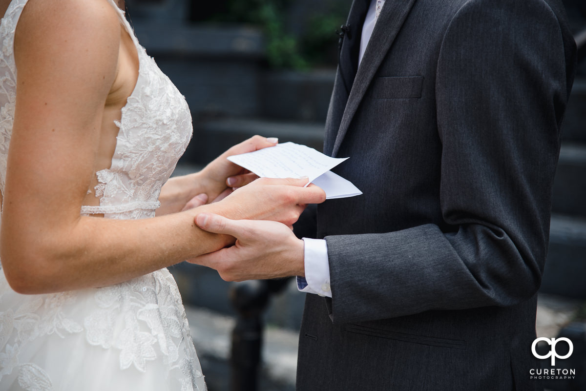 Bride and groom holding hands as they read each other letters before their wedding.