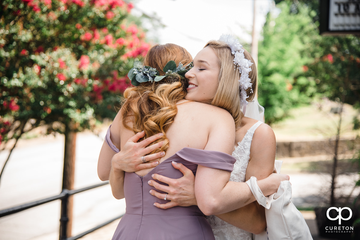 Bride hugging her maid of honor before the wedding.