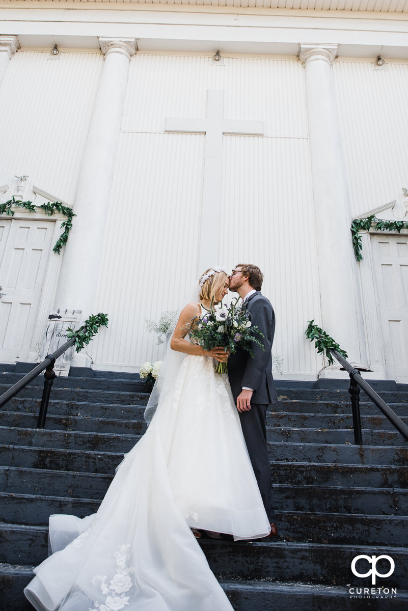 Groom kissing his bride on the forehead on the steps of Grace and Peace church before the wedding ceremony.