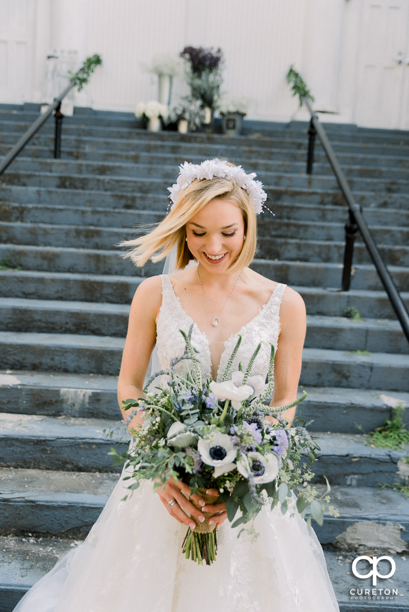 Bride holding her bouquet on the steps of a church as her hair blows into the wind.