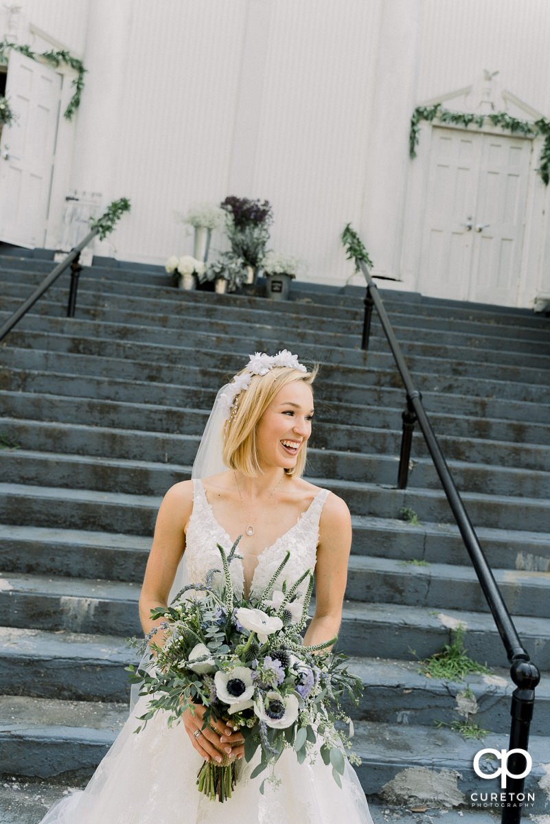 Bride laughing on the steps of the church before the ceremony.