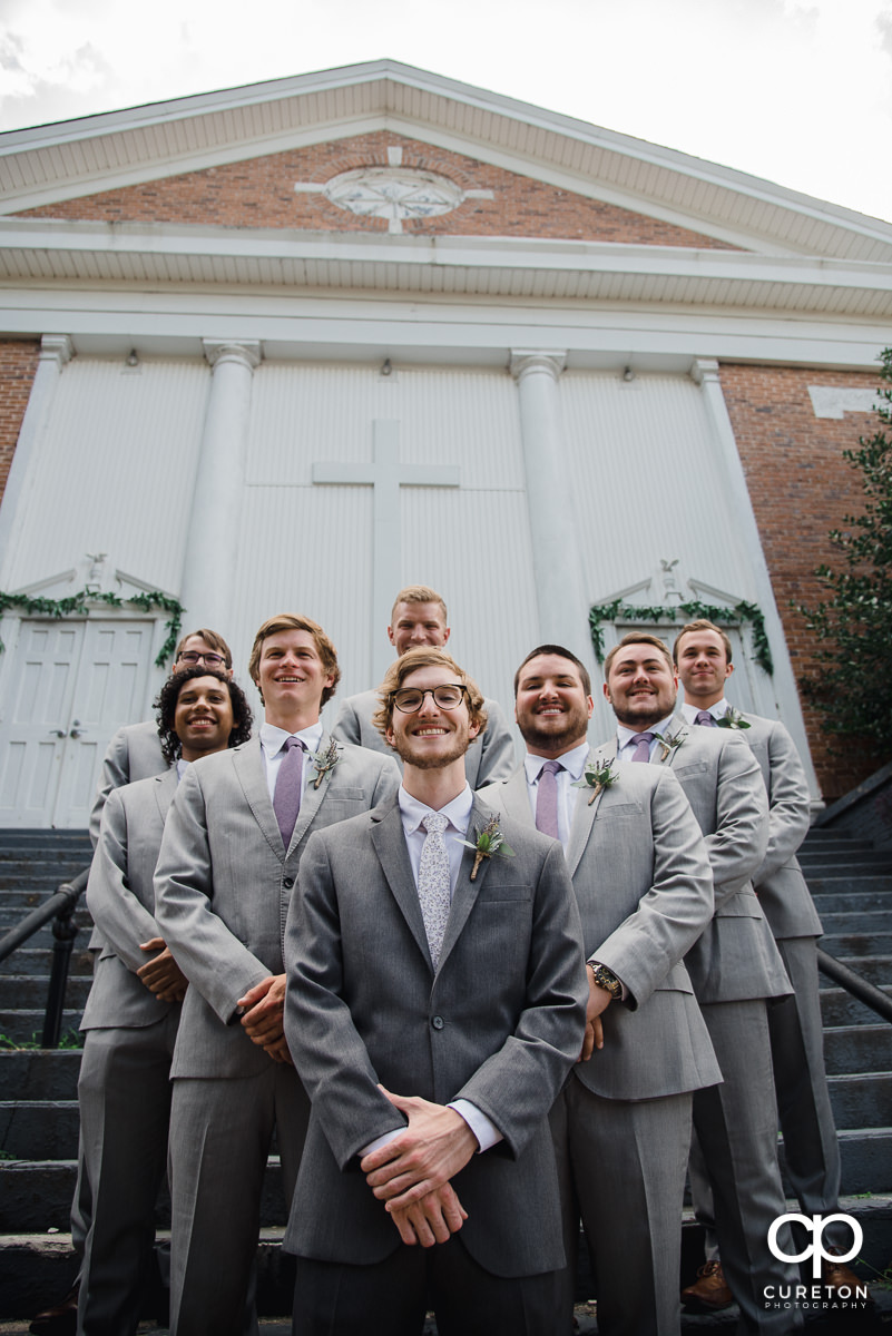 Groom and the groomsmen standing on the steps of the church.