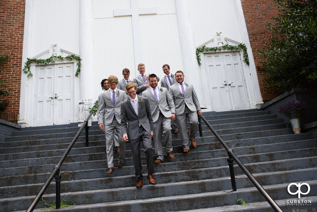 Groom and groomsmen walking down the steps at the church before the ceremony.