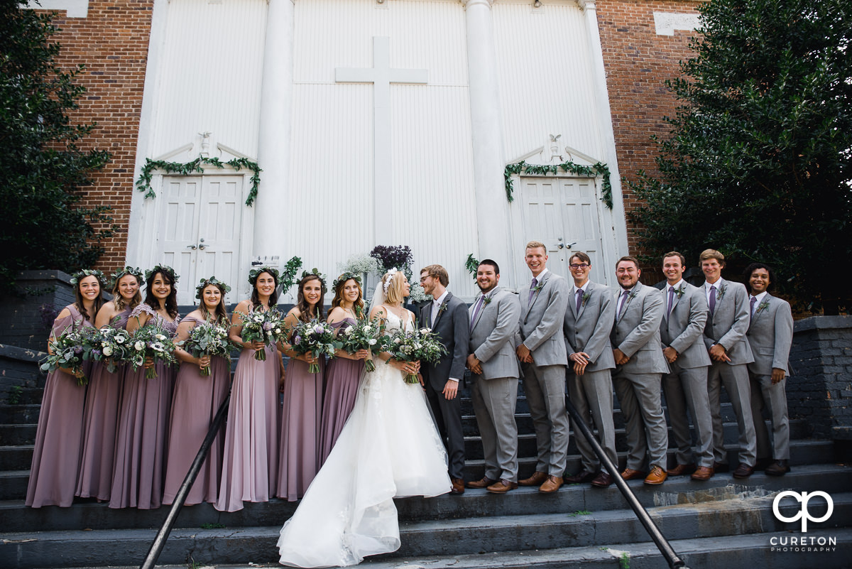 Bride and groom with their wedding party on the steps of the church before their wedding ceremony in Greenville,SC.