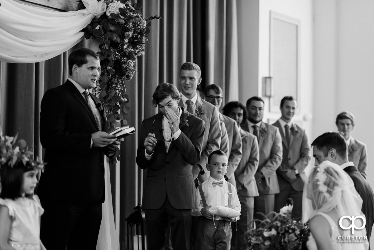 Groom getting emotional as he sees his bride walking down the aisle at their wedding.